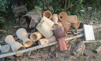 Photo of drums in various stages of being carved from single pieces of wood
