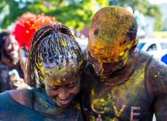 Photo of a man and a woman smiling and covered in paint