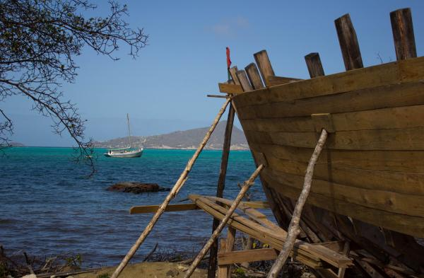 Wooden boat under construction on Carriacou with view across the water to Petit Martinique